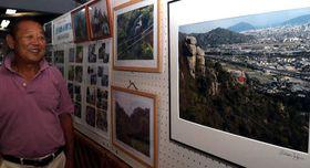 右田ケ岳の山頂から見下ろす風景について話す岡村会長
