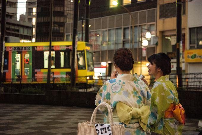 路面電車を横目に浴衣姿で涼む女性たち。温泉街の風景のようにも見えるが、実は都内だ(東京都豊島区のJR大塚駅前で)