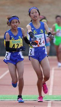 女子第4中継所。長与の4区中尾(右)からたすきを受けて走りだすアンカー久松咲=希望が丘文化公園陸上競技場