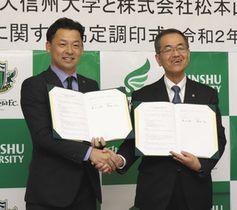協定書に調印して握手する神田社長(左)と濱田学長=松本市の信大松本キャンパスで