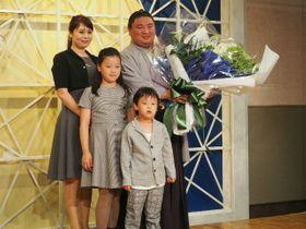 引退会見で家族から花束を渡され、記念撮影に応じる元関脇・嘉風の中村親方=16日、東京都内のホテル