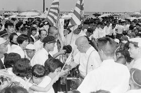 第40回全国高校野球選手権大会で準優勝し、小松島港で大勢のファンに出迎えられる徳島商の選手たち。板東英二投手と原菊太郎知事が握手する場面が捉えられている=1958(昭和33)年、本社所蔵写真