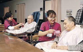 利用者の介助に当たるハンさん(右から2人目)とズンさん(左)=穴水町内の福祉施設