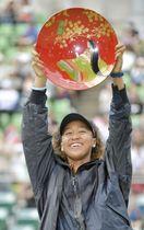 女子テニスの東レ・パンパシフィック・オープンのシングルスで大会初制覇を果たし、笑顔で優勝杯を掲げる大坂なおみ。3歳まで育った地元大阪で日本開催のツアー大会初優勝を飾った=22日、大阪市のITC靱テニスセンター