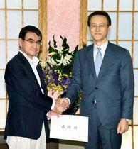 西日本豪雨被害の義援金の目録を受け取り、握手する河野外相(左)と韓国の李洙勲駐日大使=23日午前、外務省(代表撮影)