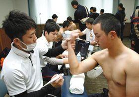 肘と肩の検診を受ける高校球児(右)ら=金沢市鞍月の県地場産業振興センターで
