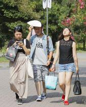 厳しい暑さの中、千葉市内を歩く人たち=21日午後
