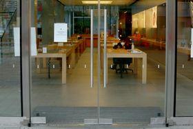 北京にあるアップルの店舗。新型肺炎の影響で閉店となり、中にはマスクをした警備員が座る=4日(UPI=共同)