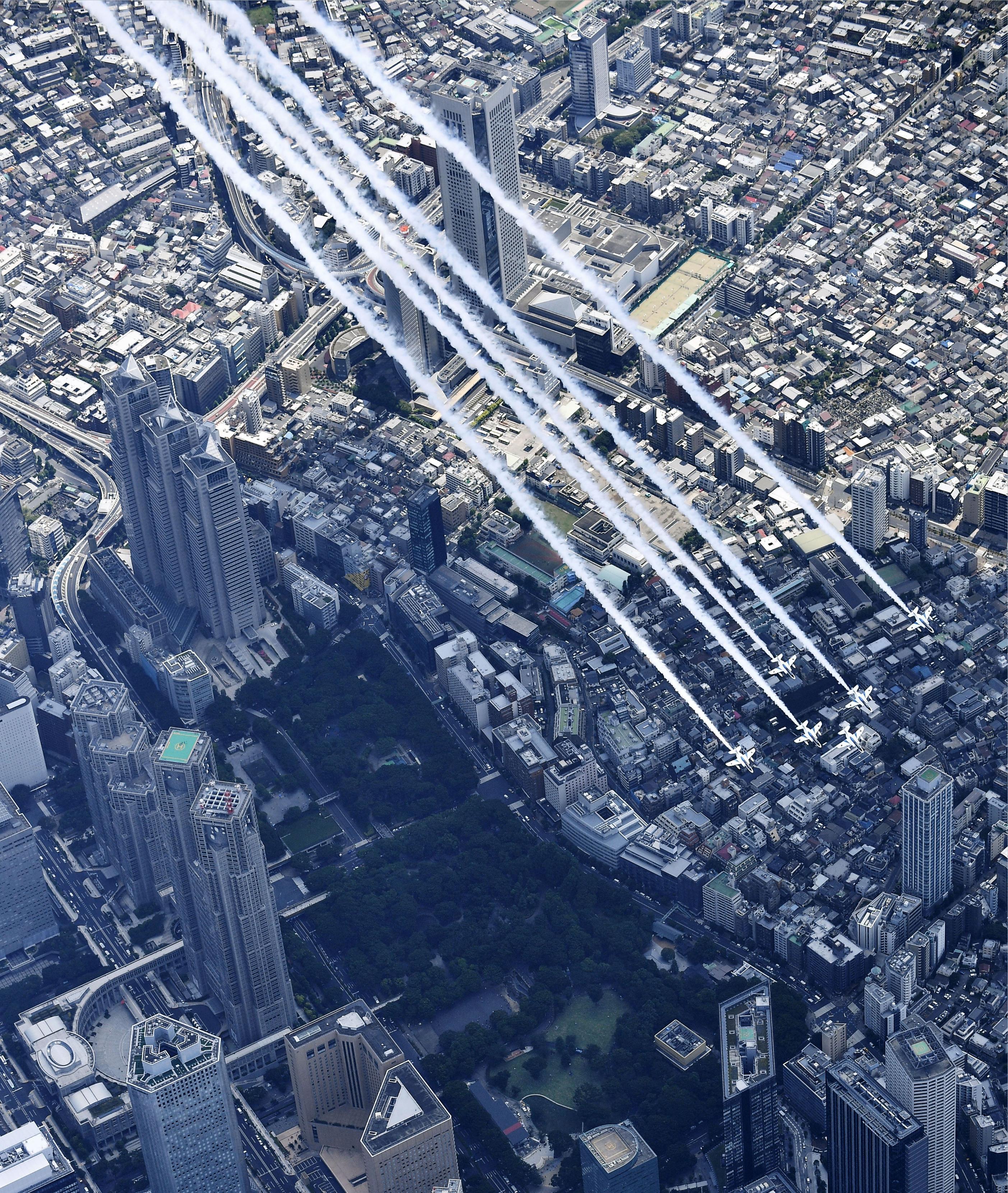 医療従事者に敬意を示すため、東京都庁(左)上空を飛行する航空自衛隊のブルーインパルス=29日午後、東京都新宿区(共同通信社ヘリから)