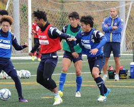 選手へ考えることを意識させ練習させる沖縄SVの選手兼監督の高原直泰(右)=18日、金武町フットボールセンター