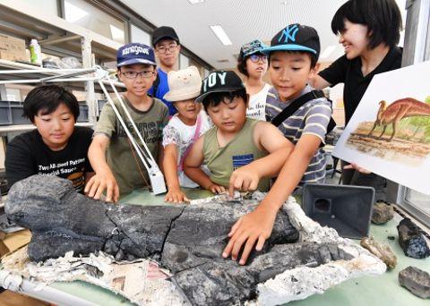 草食恐竜ハドロサウルス類の大腿骨とみられる化石を観察する子どもたち=薩摩川内市鹿島