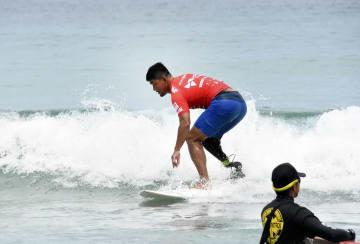 義足でサーフィンをするイベントの参加者=7月7日、静岡県下田市