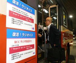 ラジオ放送を告知するステッカーが張られたバスに乗り込む乗客(撮影・大川万優)