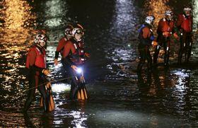 大阪市と堺市との間を流れる大和川を捜索する消防隊員ら=23日午後6時43分