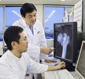 骨折した患者の検査画像を見る富山市民病院の澤口毅副院長(奥)と重本顕史高齢者骨折センター長