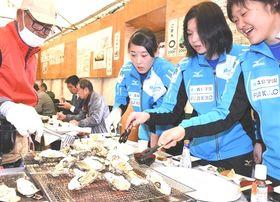 浜名湖産のカキを焼いて試食するブレス浜松の選手=15日午前、湖西市新居町の海湖館
