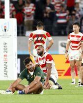 ラグビーW杯準々決勝で南アフリカに敗れ、ピッチにひざまずく日本代表のリーチ主将(中央)=20日夜、東京都調布市の味の素スタジアム