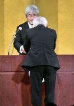 京都大の山極寿一学長(奥)から学位記を受け取る62歳の男性=26日午前、京都市