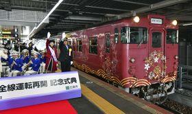 全線運転再開の記念式典が開かれ、JR広島駅を出発する芸備線の車両=23日午前