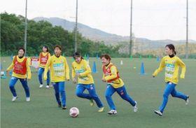 全体練習を再開し、笑顔でプレーする吉備国大シャルムの選手たち=吉備国大楢井グラウンド
