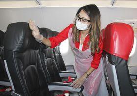 マスクや手袋などを着用し、機内の座席を消毒するエアアジア・ジャパンの従業員=9日、中部空港