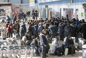 昨年12月20日、帰国のためロシア・ウラジオストク空港で搭乗手続きを待つ北朝鮮労働者(共同)