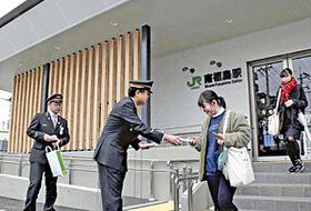利用者に記念のボールペンを配る駅員ら=福島市・南福島駅