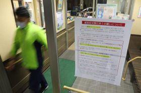 面会を必要最小限とするよう求める張り紙が掲示された有料老人ホームの玄関=25日午後、宮崎市島之内