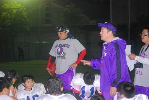 練習後、子どもたちに語りかけるOSAKAマーヴィーズの小段監督(右から2人目)=10月20日、大産大付高グラウンド