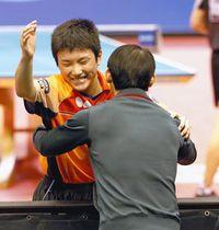 男子シングルス決勝で優勝を果たし、父親の張本宇コーチに抱きつく張本智和(左)=東京体育館で