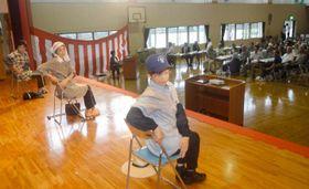 愛治地区の高齢者を前に椅子での健康体操を実践する鬼北町職員