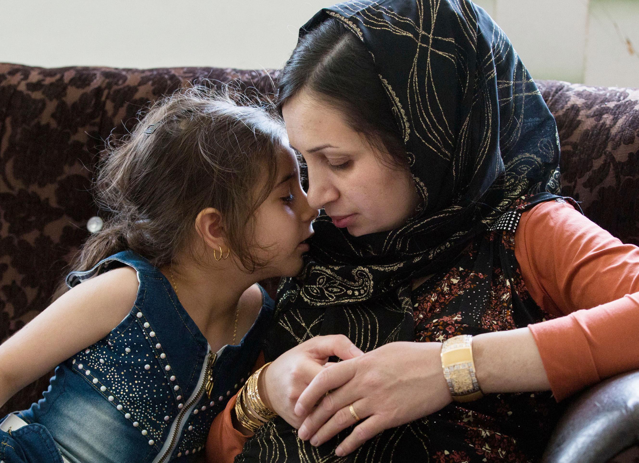 イラン北西部バネの自宅で娘のゲラレとくつろぐチマン・サイドプール。「この子が私の痛みを忘れさせてくれるの」(撮影・澤田博之、共同)