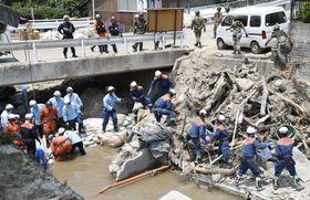 広島市安芸区矢野東で川に土のうを積み上げる消防隊員ら=17日午後