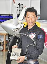 機体の前で優勝トロフィーを持つ室屋選手=福島市・ふくしまスカイパーク