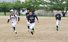 笑顔で練習に取り組む白いユニホームの庄内総合の選手と、青いユニホームの酒田光陵の選手=庄内町・庄内総合高