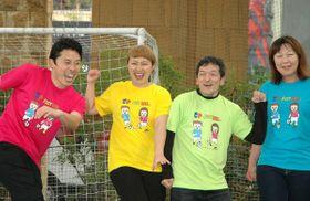 キャラクターをデザインした丸山さん(左から2人目)。Tシャツを着て発表に臨んだ=川崎市川崎区