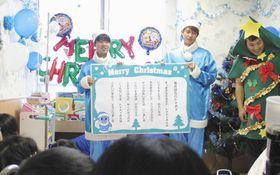 フロンターレカラーの「青いサンタ」姿で小児病棟を訪れた車屋選手(中)と原田選手(左)=中原区で