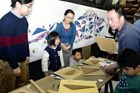 曲山社長(右)の指導で粘土を切り取る参加者ら(後方は完成イメージ)