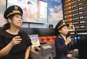 「飛行機カラオケ」を楽しむ親子。専用ルームは操縦機のレプリカなどで飾られている=東京都港区で