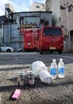 火災があったソープランドの近くには、花束や缶ビールなどが供えられていた=18日午前、さいたま市大宮区