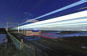 宮川の鉄橋を渡り、伊勢市駅方面(奥)へ向かう近鉄特急。窓明かりが光跡を残し走り抜けた=三重県伊勢市で