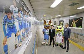 地下通路に設置されたパネルを眺める折茂代表(右)と小野寺監督