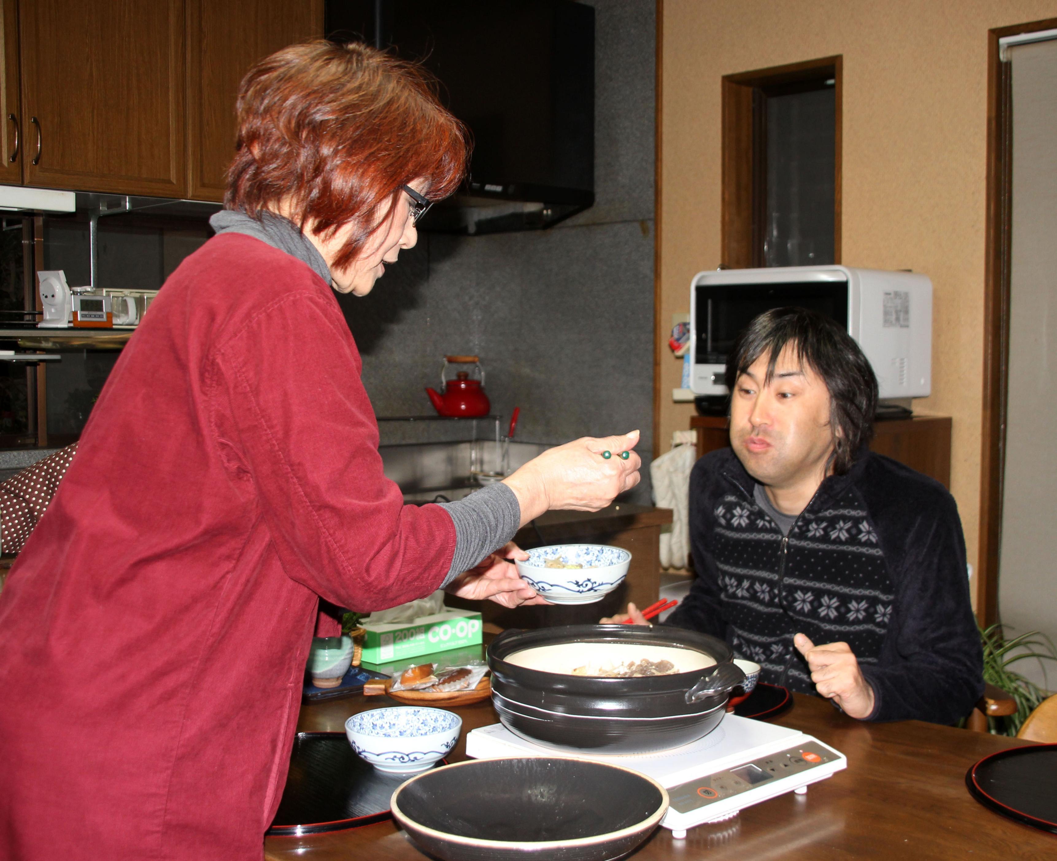 障害がある次男健治(右)に夕食をよそう福井公子、この日は健治の好物のすき焼きだ=徳島県阿波市