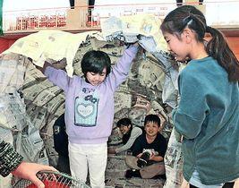 新聞紙をつなぎ合わせて作ったドームで遊ぶ子どもたち