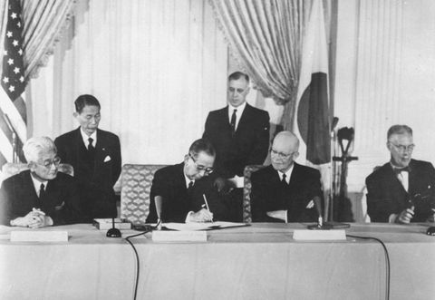 1960年1月、現行の日米安全保障条約に署名する岸信介首相(中央左)と見守るアイゼンハワー大統領(同右)。左端は藤山愛一郎外相、右端はハーター国務長官=ワシントンのホワイトハウス(AP=共同)