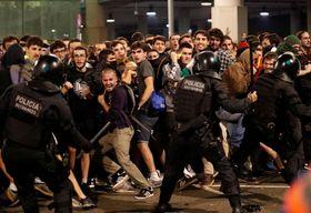 14日、スペイン・バルセロナの空港でデモ隊と衝突する警官ら(ロイター=共同)