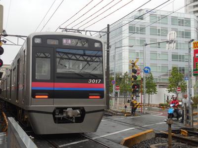 八幡駅に到着する、うすい行き普通電車。右奥が新しい京成電鉄本社