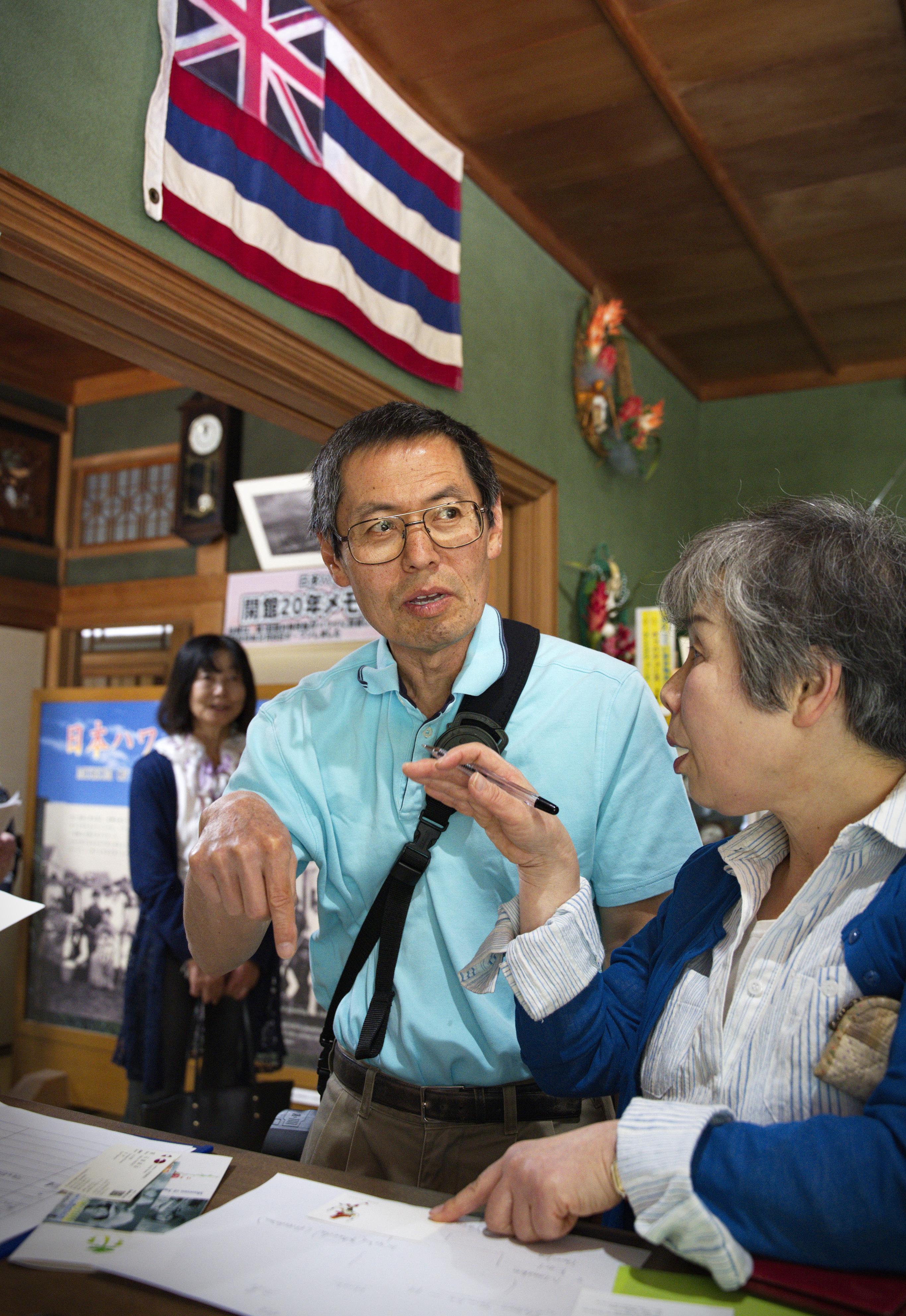 日本ハワイ移民資料館を訪れたヨネオカ・ヤスシ・エドウィン(左)。資料館にはハワイ州旗が飾られ、日系人たちが使った日用品などが展示されている=山口県周防大島町