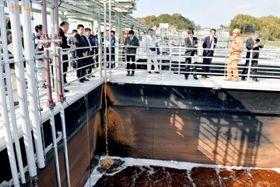 完成した水処理施設の貯留槽を見学する関係者=20日午後、松山市菅沢町