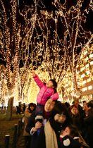 「SENDAI光のページェント」で、ケヤキ並木を彩るイルミネーションを楽しむ親子=14日夜、仙台市